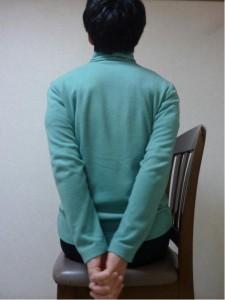 背中の後ろで指を組んでいる写真